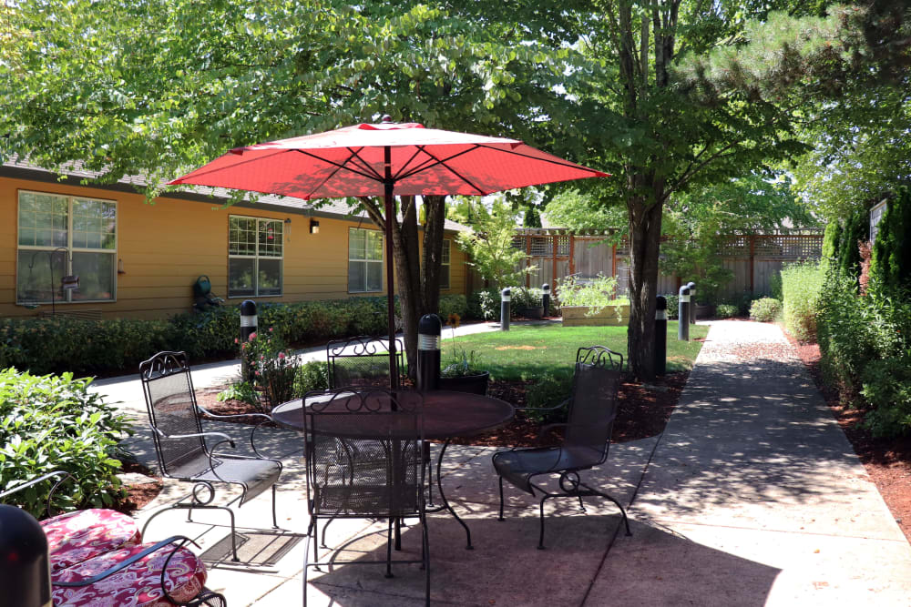 Outside patio seating on a sunny day complete with bright red umbrella at The Springs at Willowcreek in Salem, Oregon
