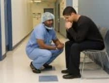 Man sitting in a hospital with a nurse