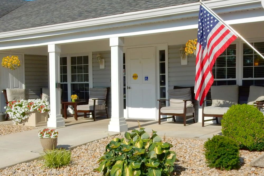 Sunny front porch of upscale senior living facility complete with seating and American flag  at Carriage Court of Grove City in Grove City, Ohio