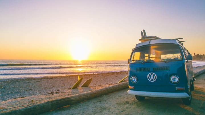 A Volkswagen van parked on the beach at sunset with surfboards attached to the roof and along the side of the van.