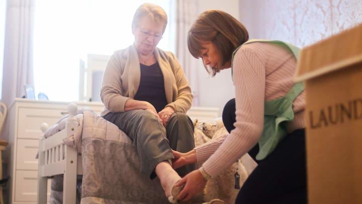 Caregiver assisting senior putting on shoes