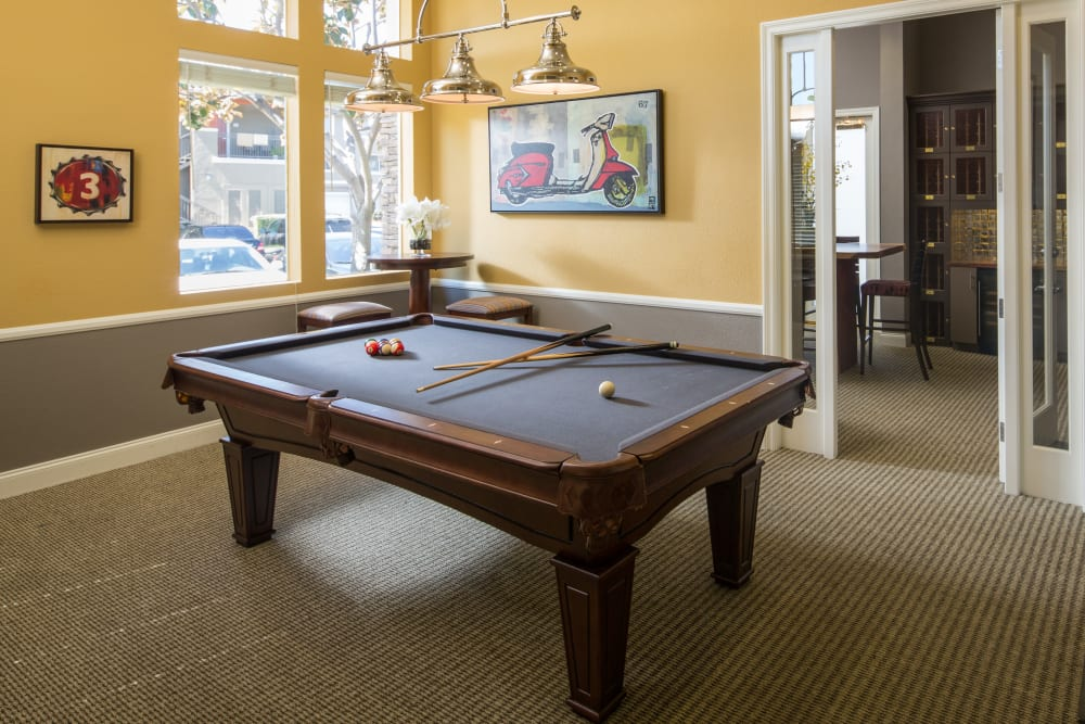 Interior view of the resident clubhouse with a billiards table at Alicante Apartment Homes in Aliso Viejo, California