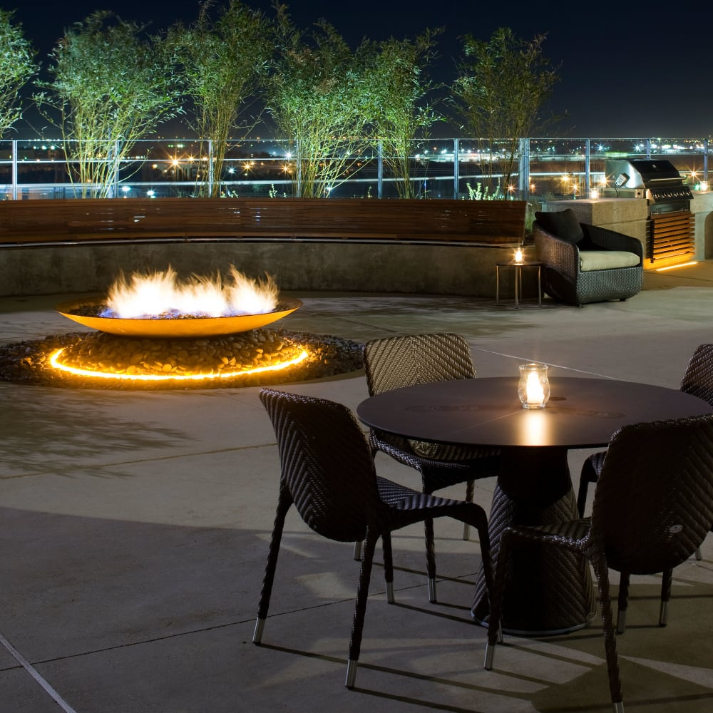 Beautiful outdoor seating at night next to propane fuel fireplaces at The Heights at Park Lane in Dallas, Texas