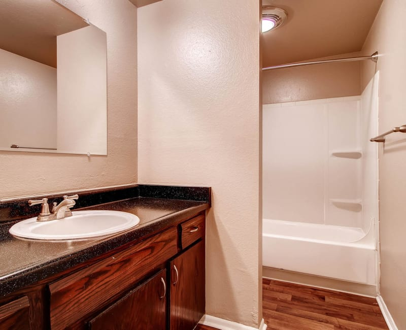 Bathroom with wood-style plank flooring at Arvada Green Apartment Homes in Arvada, Colorado