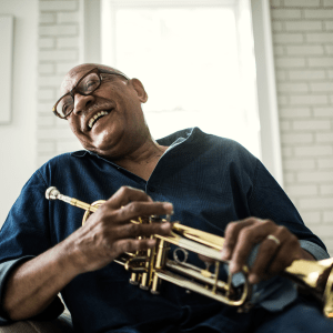 Laughing resident holding a trumpet at Hanover Place in Tinley Park, Illinois