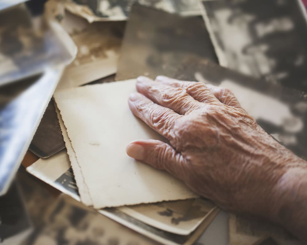 resident with their hand on a stack of papers at The Hearth at Greenpoint in Liverpool, New York