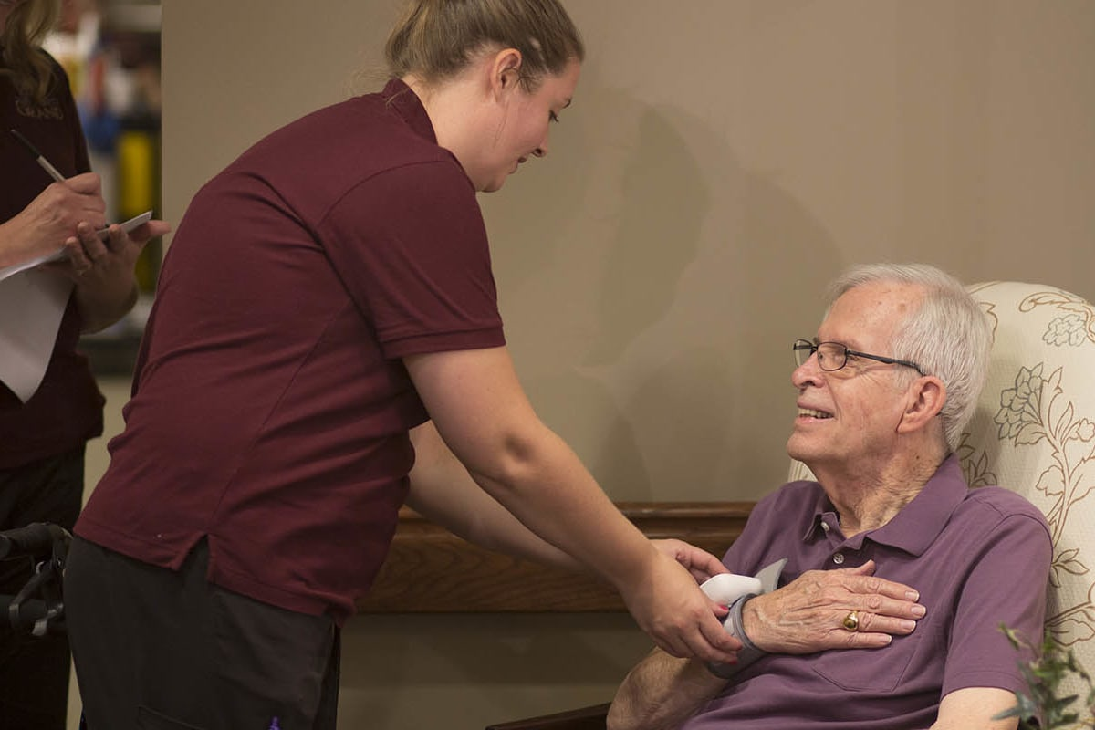 A resident and staff at Oxford Glen Memory Care at Grand Prairie in Grand Prairie, Texas