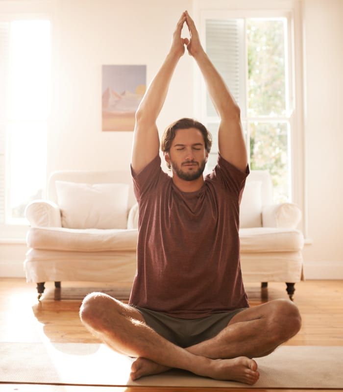Resident doing yoga in his bedroom at Oaks Lincoln Apartments & Townhomes in Edina, Minnesota