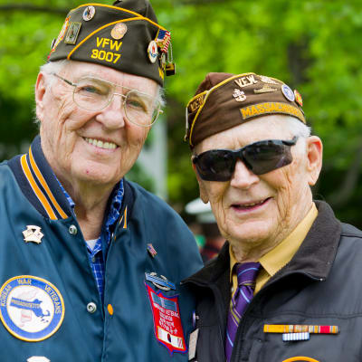 Two veteran residents smiling outside at Wildwood Manor Apartments