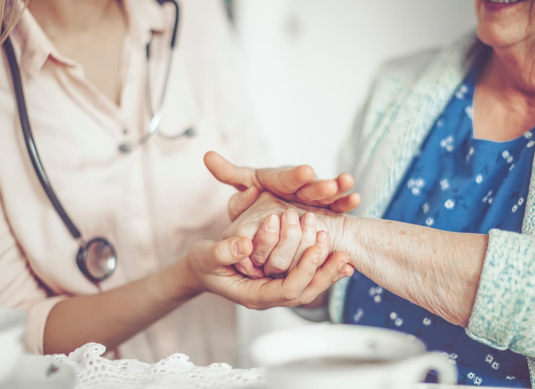 A nurse from At Home Care Group holding a resident's hands.