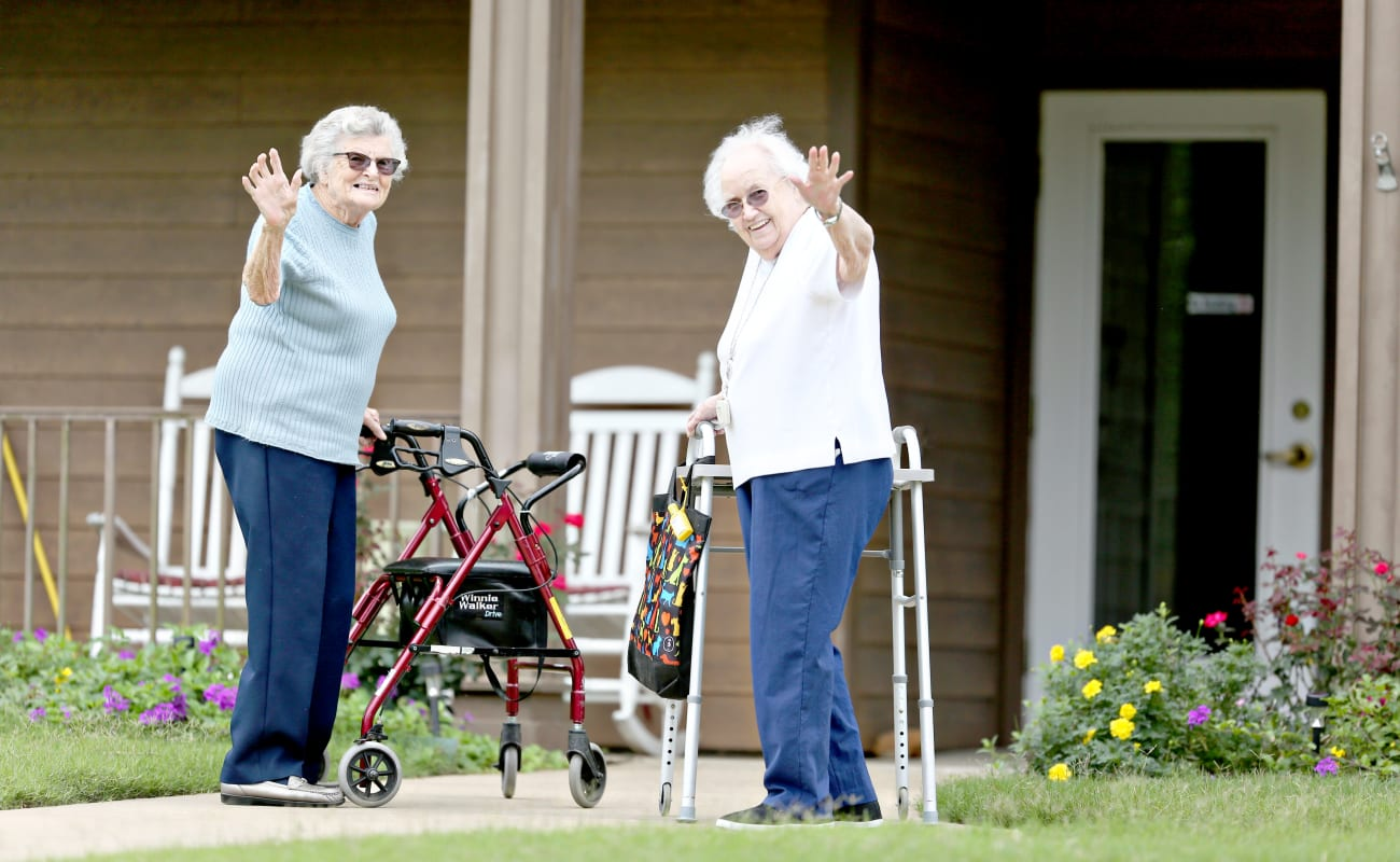 Two resident friends waving hello on their walk at Providence Assisted Living in Cleveland, Mississippi.