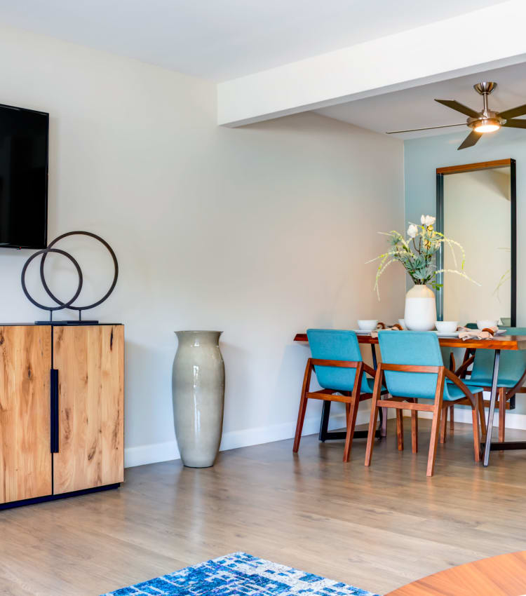 Well-decorated open-concept living space next to the dining area with a ceiling fan in a model home at Sofi Berryessa in San Jose, California