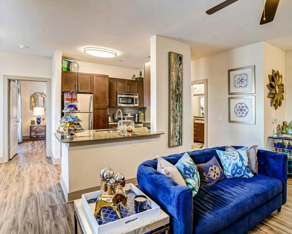 Large open-concept living area and kitchen with a breakfast bar in a model home at Sundance Creek in Midland, Texas