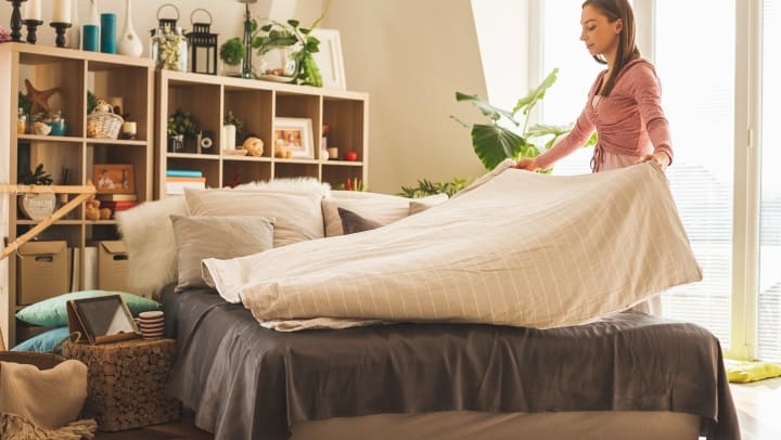 Woman making a bed at Olympus Katy Ranch in Katy, Texas