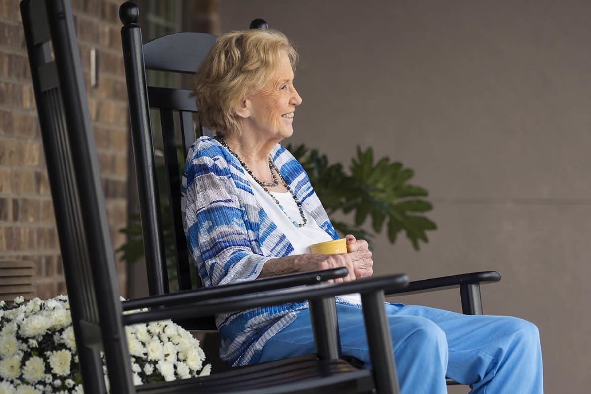 A resident enjoying her coffee outside at Oxford Glen Memory Care at Grand Prairie in Grand Prairie, Texas