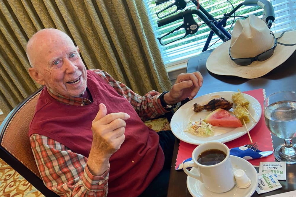 Male resident in red shirt smiling and giving thumbs up in dining room with delicious food at Azpira at Windermere