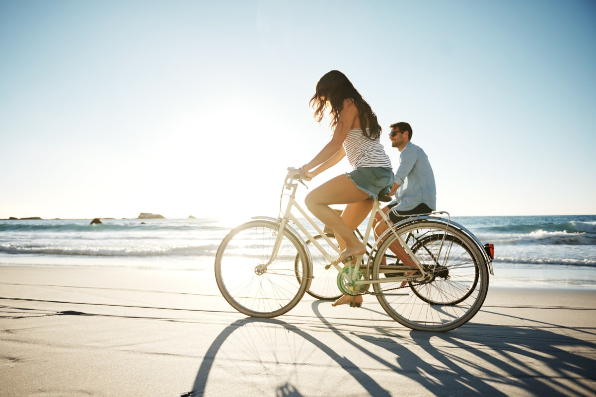 Resident couple enjoying a day bicycling at the beach near The Tides at Marina Harbor in Marina Del Rey, California