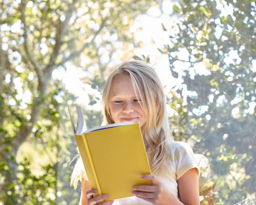 Resident child reading a book in her new home at Sofi Berryessa in San Jose, California