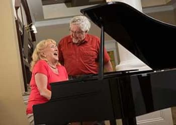 Residents playing piano at Discovery Village At Dominion in San Antonio, Texas