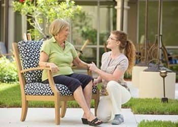 Residents talking to a caregiver at Discovery Village At Dominion in San Antonio, Texas