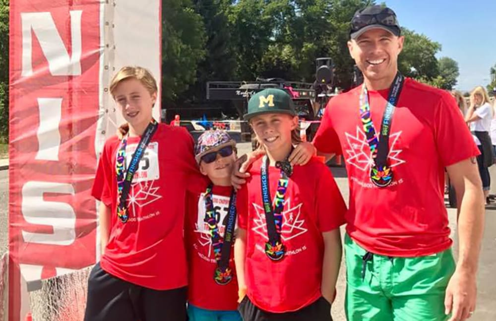 Thomas from Touchmark at Wedgewood in Edmonton, Alberta competing in a triathlon with his sons.