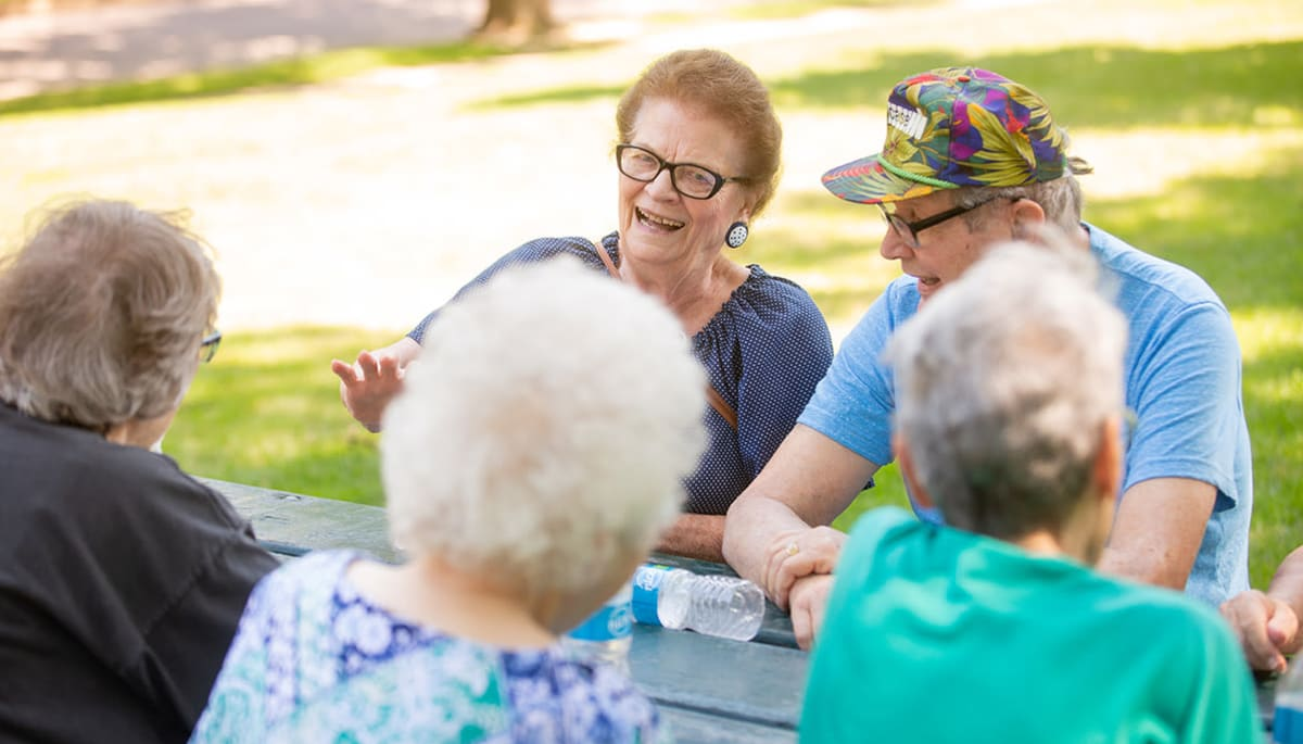 residents sitting together at an outdoor table