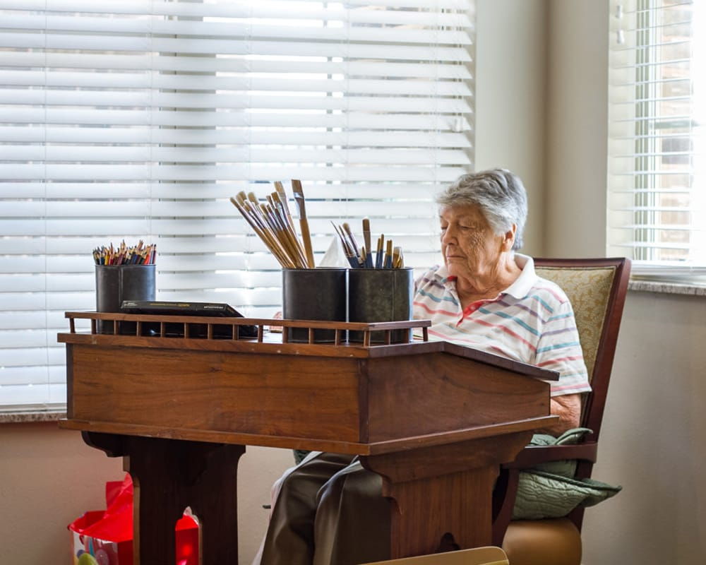 Woman resident enjoying painting at Iris Memory Care of Turtle Creek in Dallas, Texas.