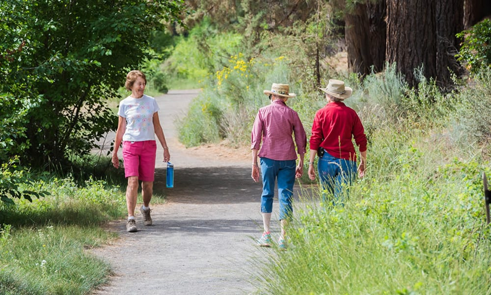 Residents hiking along a paved trail at Touchmark at Mount Bachelor Village in Bend, Oregon