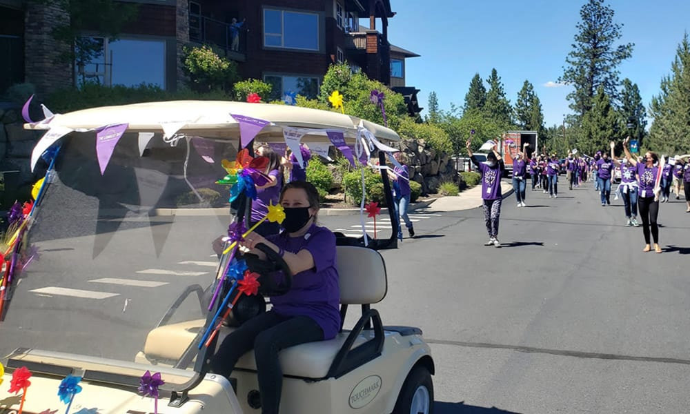 Residents waving to a parade at Touchmark Central Office in Beaverton, Oregon