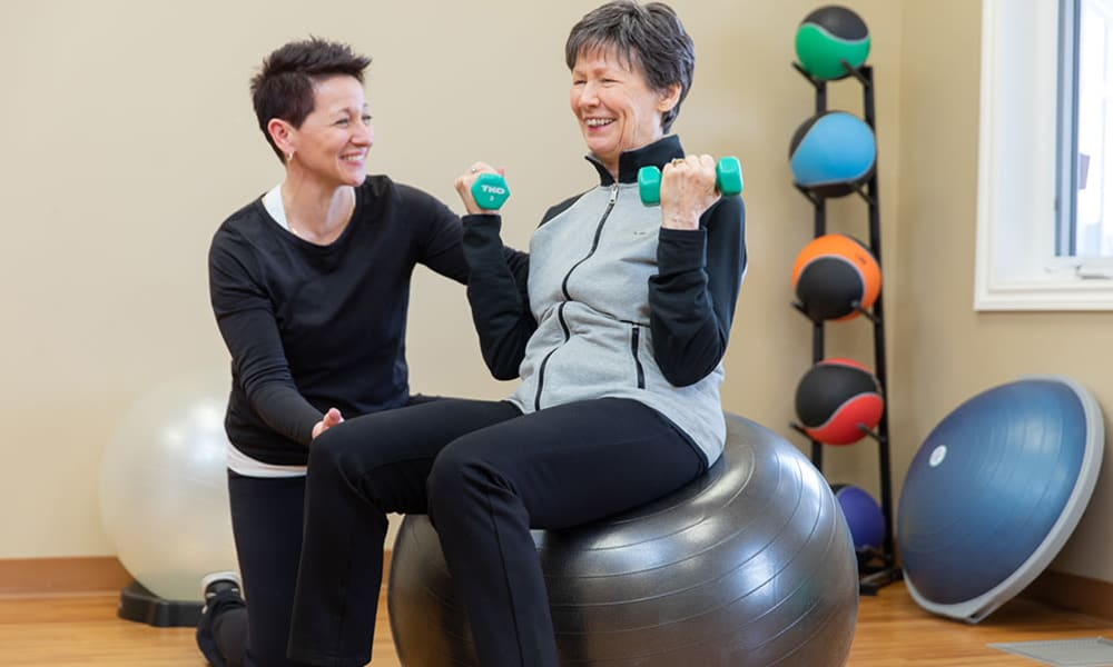 A team member and resident from Touchmark at Wedgewood in Edmonton, Alberta exercising.