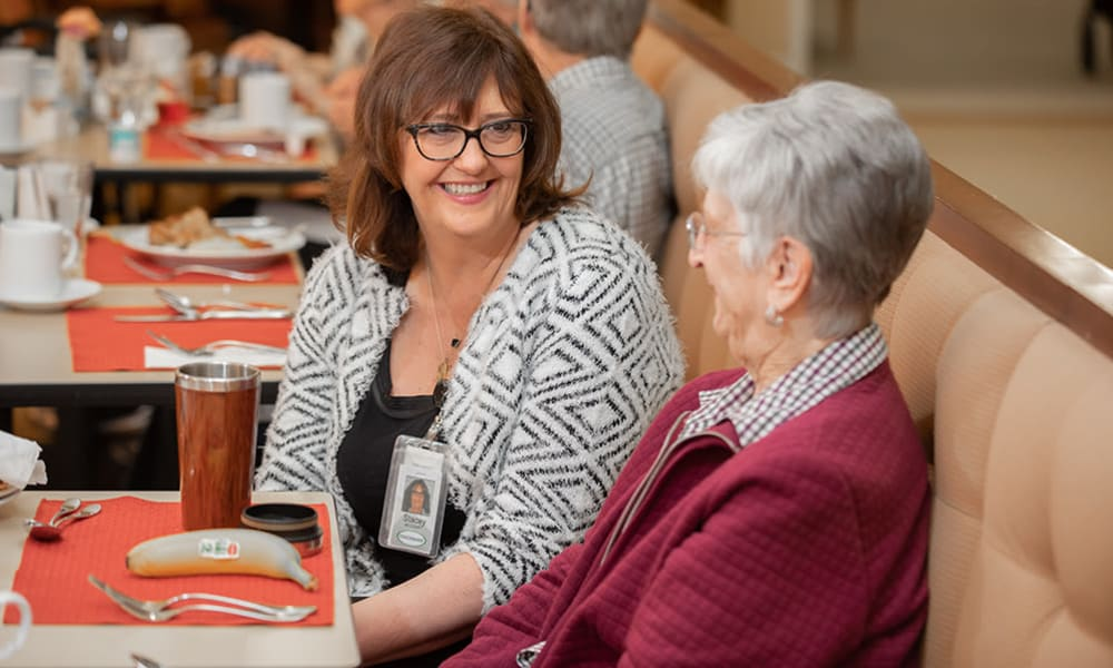 A team member chatting with a resident at Touchmark at Wedgewood in Edmonton, Alberta