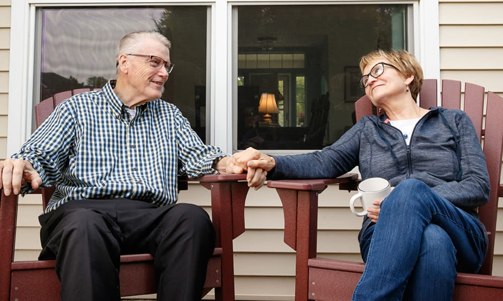 Residents sitting on a porch holding hands.