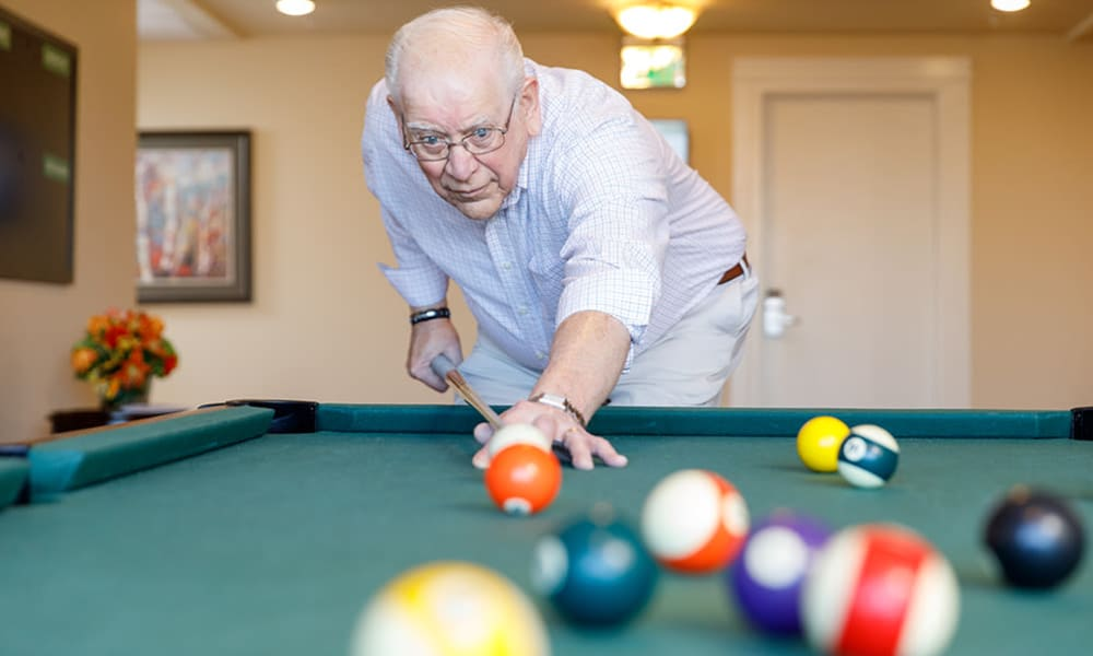 Resident playing billiards at Touchmark at All Saints in Sioux Falls, South Dakota