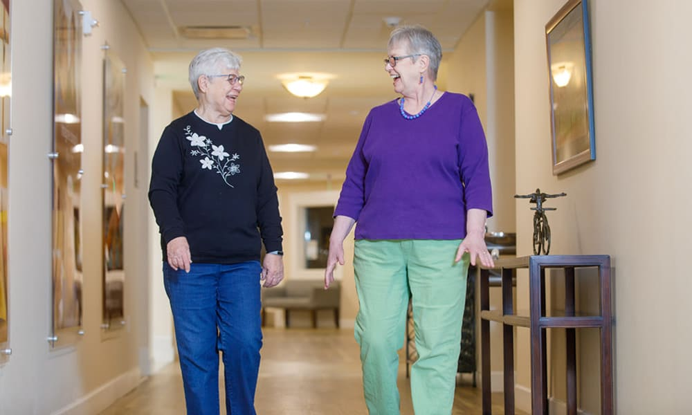 Residents from Touchmark at All Saints in Sioux Falls, South Dakota chatting as they walk down the hallway