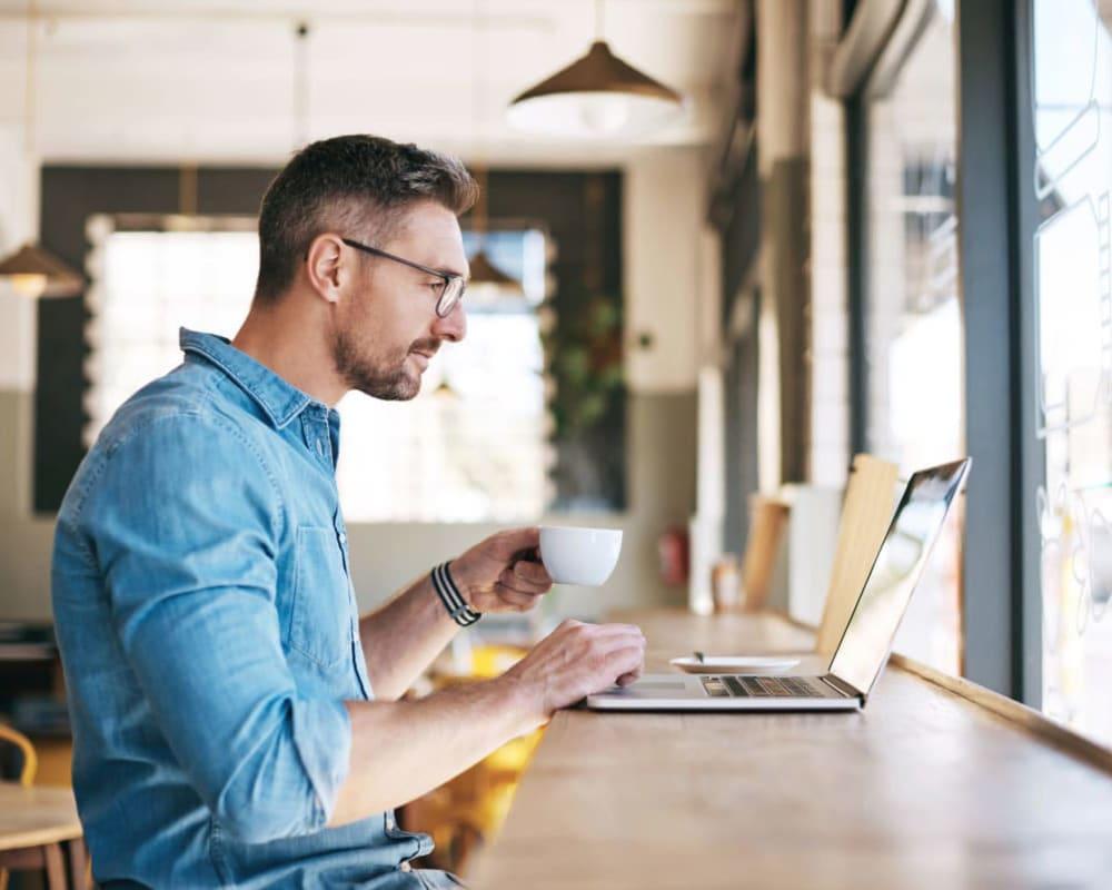 Man on his laptop at a coffee shop near Villas at Canyon Ranch in Yukon, Oklahoma