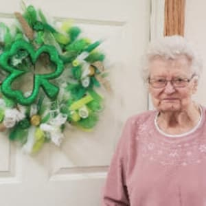 Resident Leona standing by the new wreathe she made for her Dare to Dream event at SunnyBrook Carroll in Carroll, Iowa