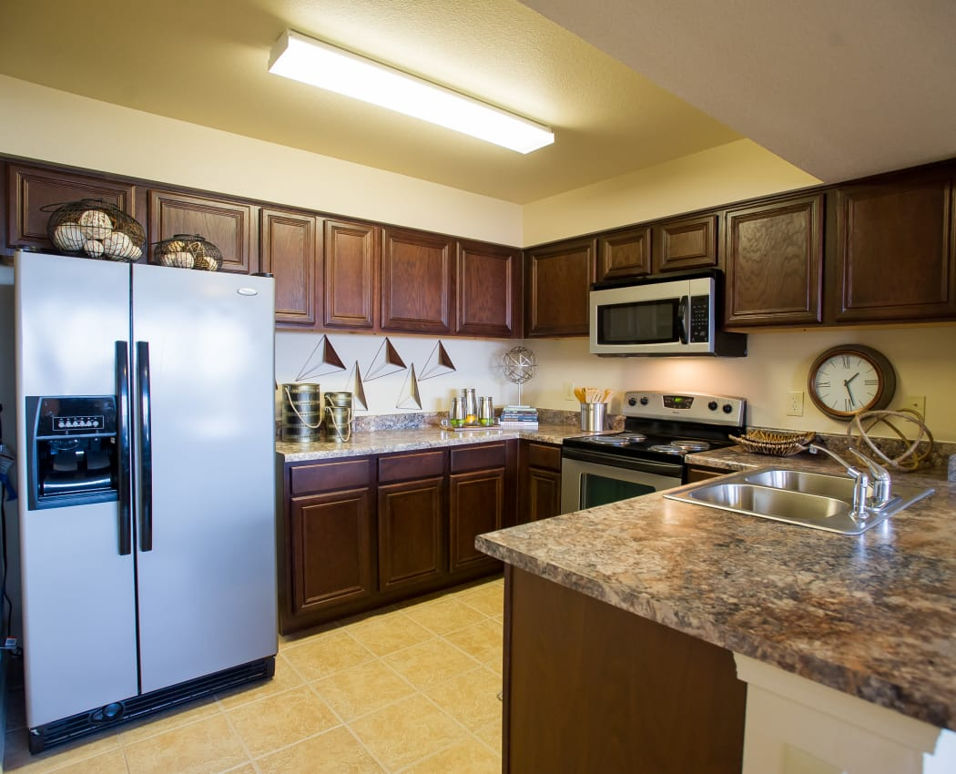 Modern kitchen with granite-style countertops at Tuscany Hills at Nickel Creek in Tulsa, Oklahoma