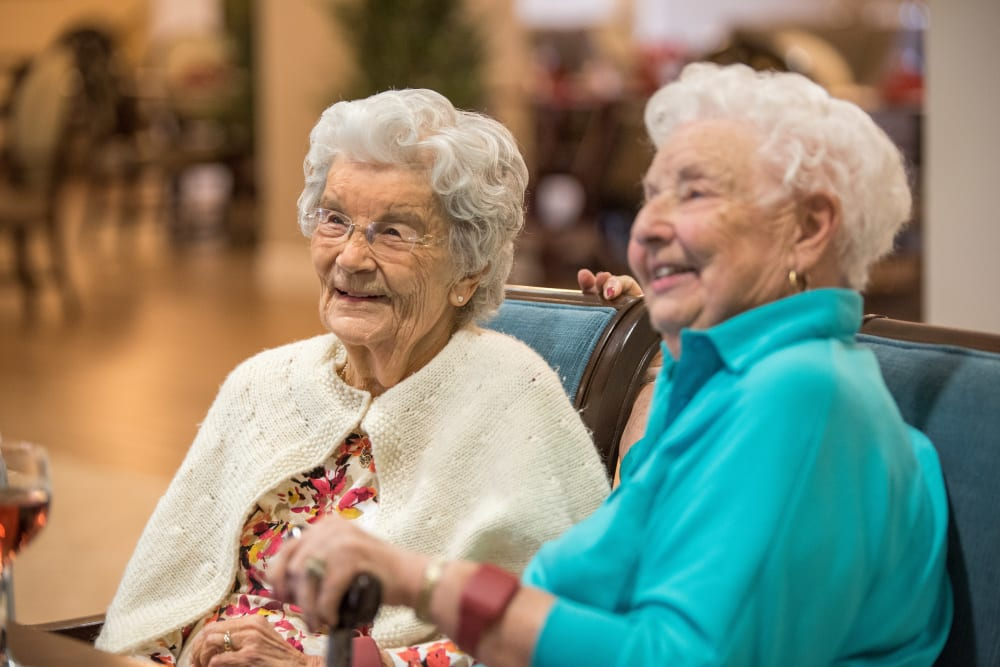 Two residents sitting on a couch at Inspired Living Sugar Land in Sugar Land, Texas.