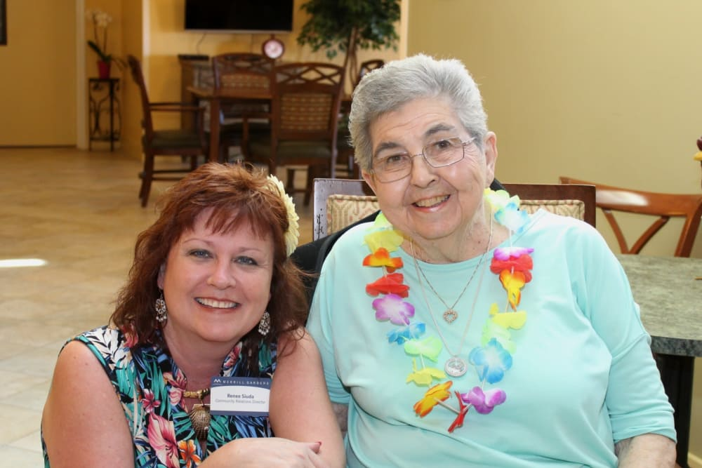 A resident and staff member at a luau at The Oaks, A Merrill Gardens Community in Gilbert, Arizona.