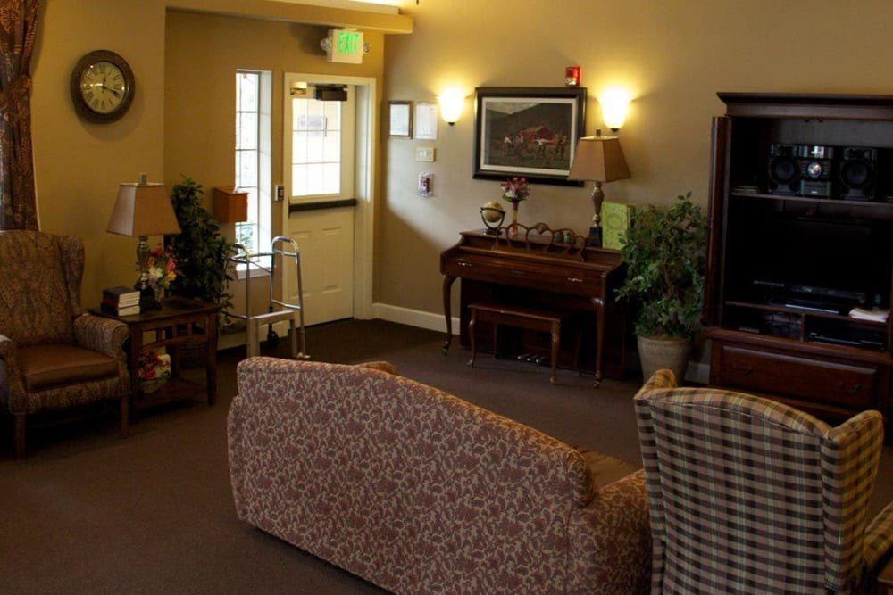 Front communal sitting area in upscale senior living facility complete with wood accented piano and armchairs at The Springs at Willowcreek in Salem, Oregon