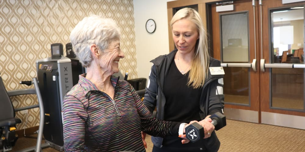 Resident lifting weights with caregiver at The Springs at Bozeman in Bozeman, Montana