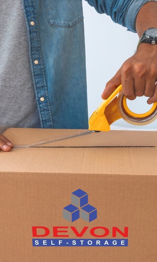 Man taping up a box to be stored at Devon Self Storage in Greenville, Texas