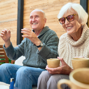 Residents sitting outside drinking coffee at Sunstone Village in Denton, Texas