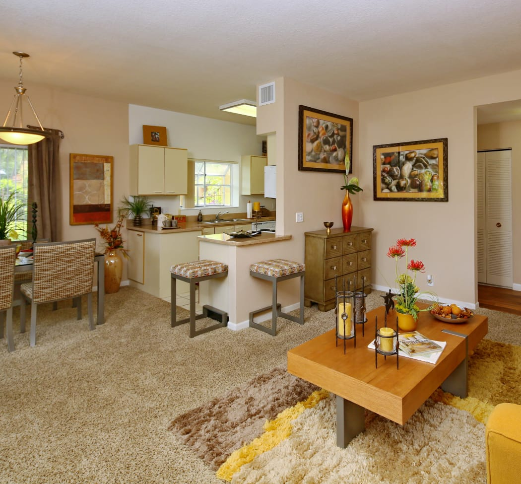 Model home living room with plush carpet looking into kitchen and dining area at IMT Pinebrook Pointe in Margate, FL