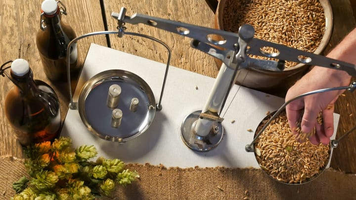 A measuring scale and other brewing materials on a wooden table. A hand drops grain onto one of the scales.
