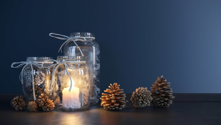 Winter scenery in mason jars with candles, pine cones, and ribbon at Olympus Solaire