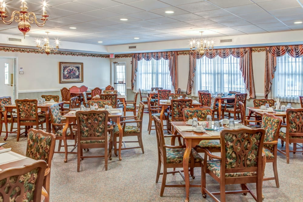 Elegant dining area with wood accents and chandeliers at Grand Victorian of Rockford in Rockford, Illinois
