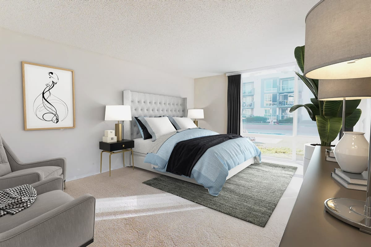 Spacious bedroom with plush carpeting and floor-to-ceiling windows at Waters Edge at Marina Harbor in Marina del Rey, California