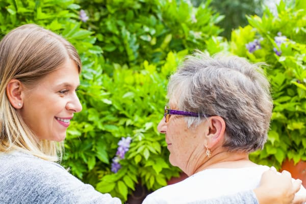 Senior woman and caregiver outside at Golden Pond Retirement Community