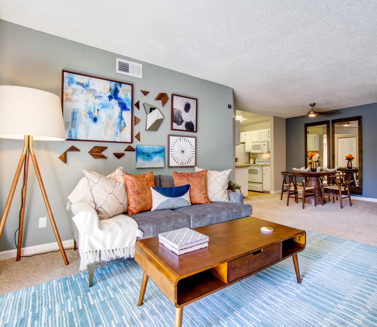 Plush carpeting and an accent wall in the well-furnished living space of a model home at Waterstone Fremont in Fremont, California